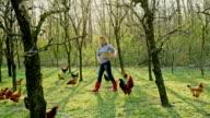 WS-Frau Fütterung Hühner im Hinterhof