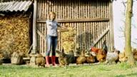 WS-Frau Fütterung Hühner auf einem kleinen Bauernhof