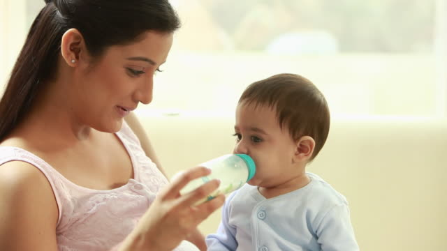 Woman feeding her baby with milk bottle