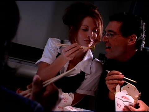 Woman feeding man Chinese takeout