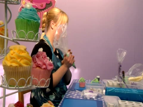 A woman finishes icing a cupcake looks up and smiles