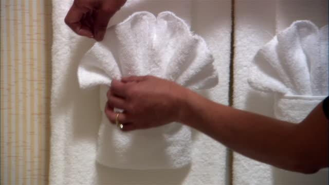 CU, PAN, Woman fixing towel arrangement in hotel bathroom, close-up of hands