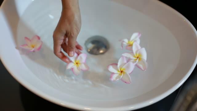 woman floating flower on washbasin