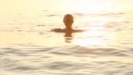Woman floats in tropical sea, at sunrise