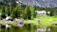 Frau Fliegenfischen in einem Mountain Pond