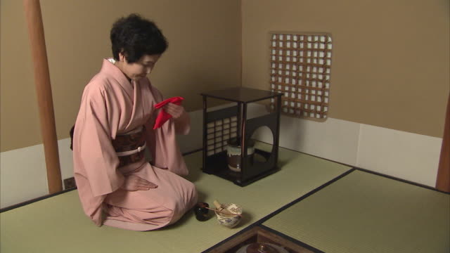 WS Woman folding red towel during tea ceremony, Tokyo, Japan