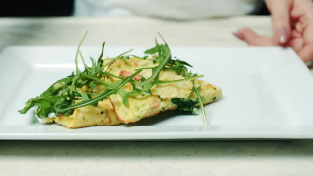 Woman Garnishing Omelet With Arugula In Plate
