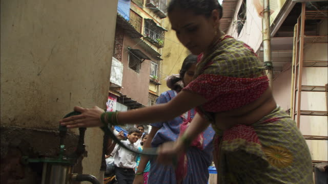 A woman gathers water with a hand pump. Available in HD.