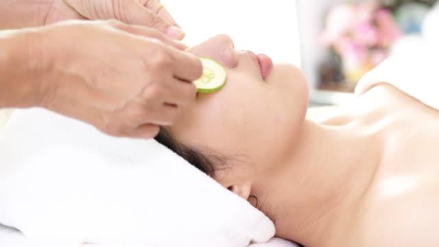 Vrouw spabehandeling, komkommers op gezicht krijgen.