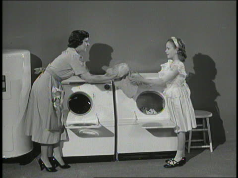 B/W woman + girl take laundry from washing machine + put it in dryer