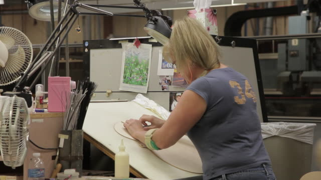 MS Woman gluing and cutting out pieces of guitar body shell on drafting table / Nazareth, Pennsylvania, USA