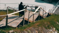 Woman goes down the wooden steps