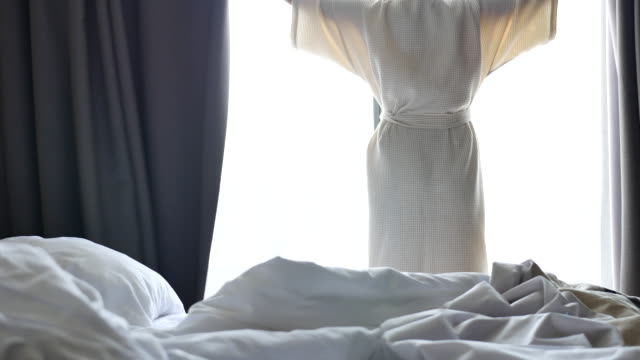 Woman Going opens the curtains in the morning