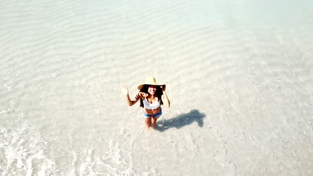 woman greeting from the beach - drone view