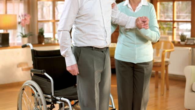 SLO MO woman guiding a senior man away from wheelchair