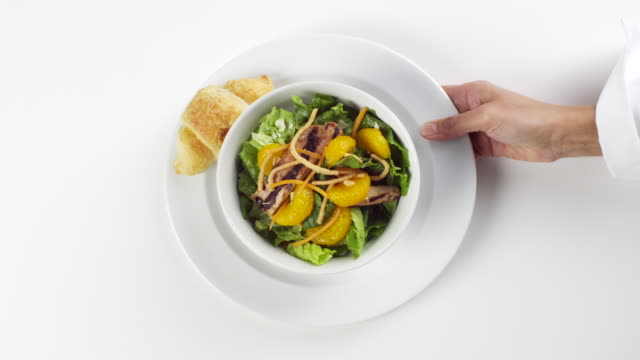 CU Woman hand entering setting down round white bowl of lettuce with mandarin oranges on top / Omaha, Nebraska, United States