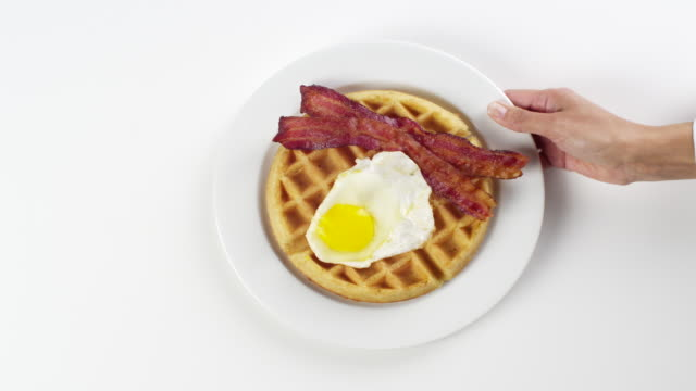 CU Woman hand entering setting down round white plate with Belgium waffle, egg sunny side and two strips of bacon / Omaha, Nebraska, United States