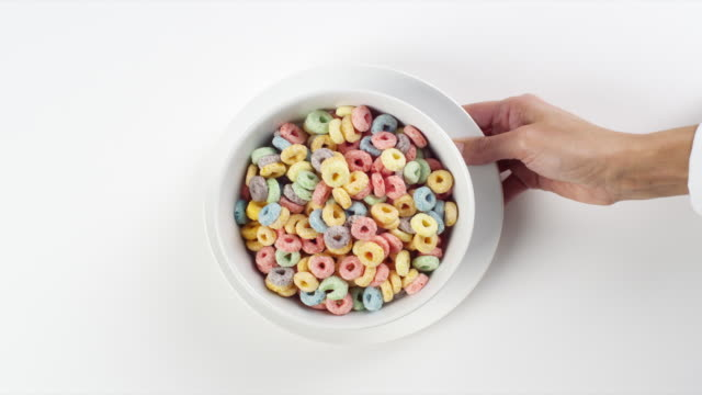 CU Woman hand entering setting down round white plate with bowl with colorful Fruit Loops breakfast cereal / Omaha, Nebraska, United States