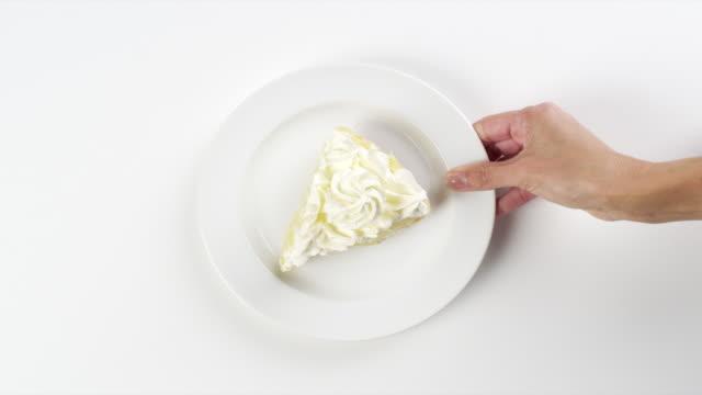 CU Woman hand entering setting down round white plate with coconut cream, banana cream slice of dessert pie / Omaha, Nebraska, United States