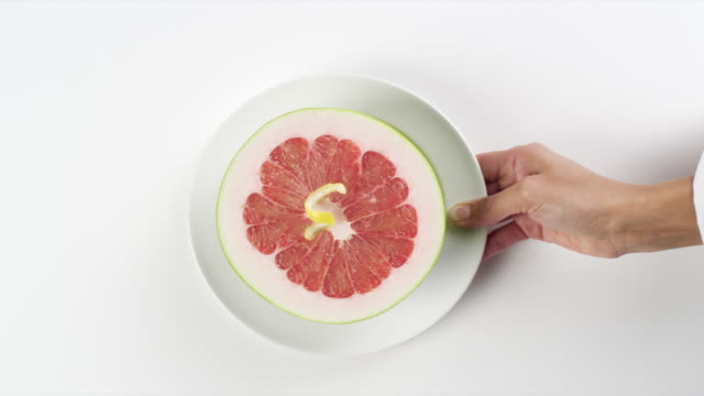CU Woman hand entering setting down round white plate with colorful half of grapefruit / Omaha, Nebraska, United States