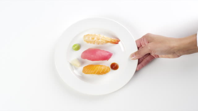 CU Woman hand entering setting down round white plate with colorful sushi raw fish and yellowtail salmon / Omaha, Nebraska, United States