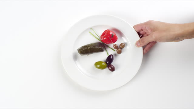 CU Woman hand entering setting down round white plate with dolma and olives / Omaha, Nebraska, United States