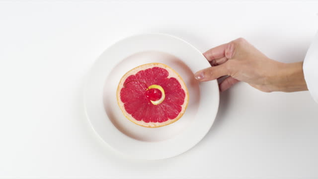 CU Woman hand entering setting down round white plate with grapefruit half healthy breakfast / Omaha, Nebraska, United States