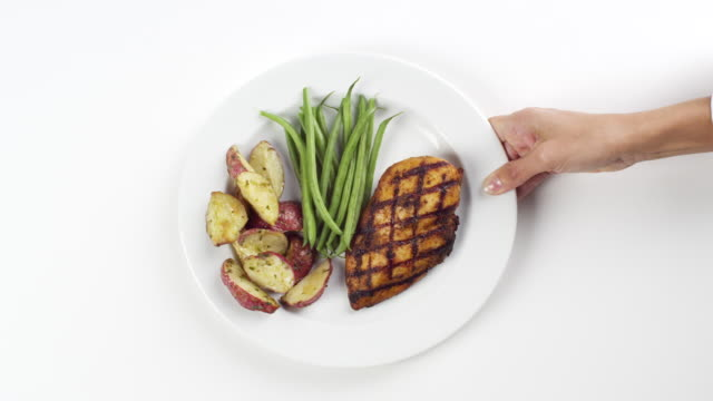 CU Woman hand entering setting down round white plate with green beans, grilled chicken breast and red fried potatoes / Omaha, Nebraska, United States