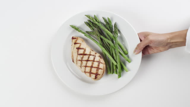 CU Woman hand entering setting down round white plate with grilled chicken breast and asparagus / Omaha, Nebraska, United States