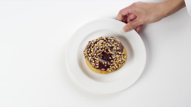 CU Woman hand entering setting down round white plate with large donut with chocolate frosting and nuts / Omaha, Nebraska, United States