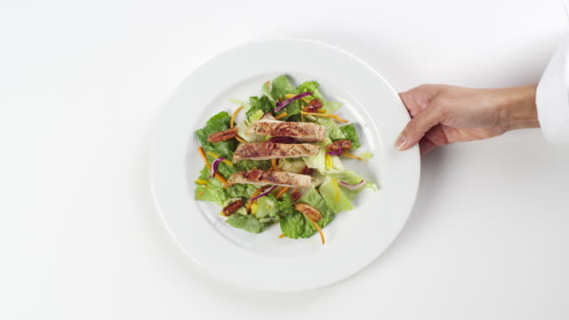 CU Woman hand entering setting down round white plate with lettuce salad and grilled chicken / Omaha, Nebraska, United States