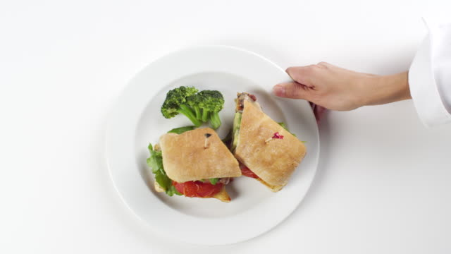 CU Woman hand entering setting down round white plate with sandwich sliced in two pieces and broccoli on the side / Omaha, Nebraska, United States