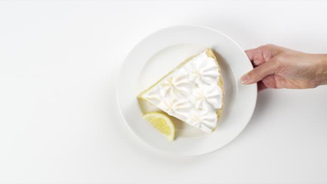 CU Woman hand entering setting down round white plate with slice of lemon meringue pie dessert / Omaha, Nebraska, United States