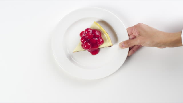 CU Woman hand entering setting down round white plate with slice of cheesecake, with red cherries dessert / Omaha, Nebraska, United States