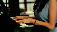 Woman hand playing piano and looking tablet