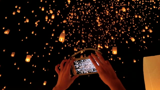 Woman hand taking sky lantern picture with Smart Phone