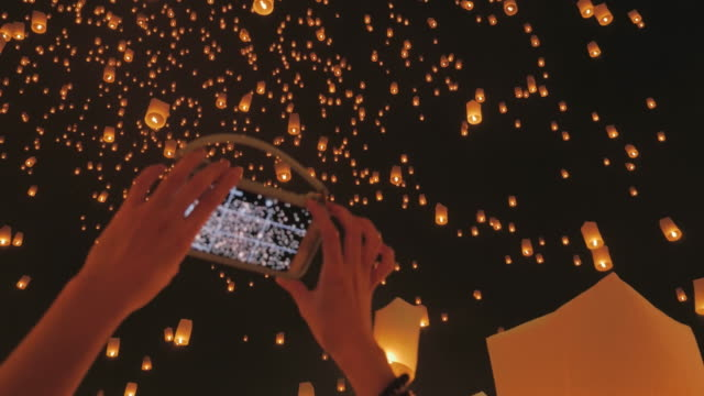 ,Woman hand taking sky lantern picture with Smart Phone