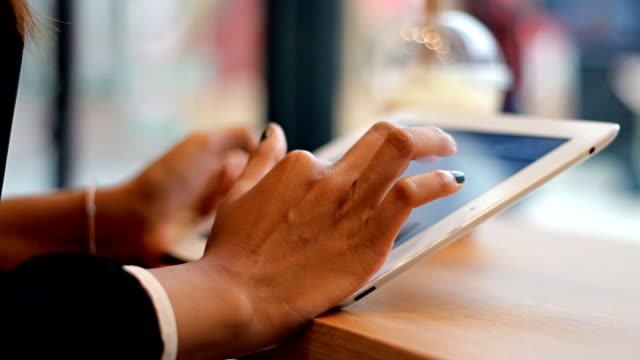 Woman hand using digital tablet at coffee cafe