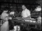 B/W 1932 woman handing scrip to male pharmacist behind counter in pharmacy / Merced, CA