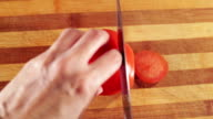 Woman hands cutting a tomato