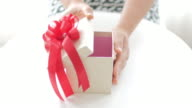Woman Hands open a gift box on white table