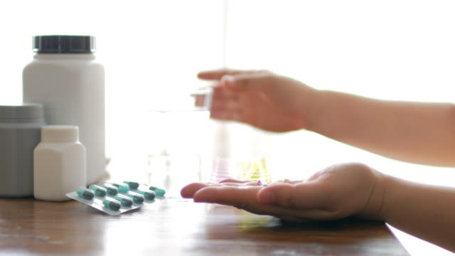 Woman hands take a medicine with drinking water , dolly shot