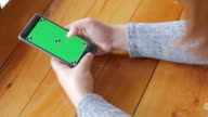 Woman hands touching smartphone with green screen display , dolly shot