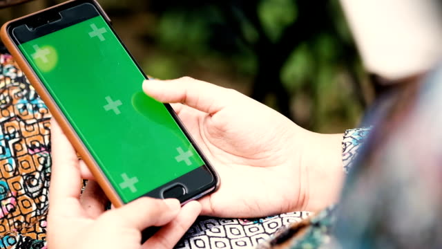 Woman hands touching smartphone with green screen display