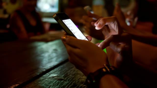 woman hands using smart phones at the bar