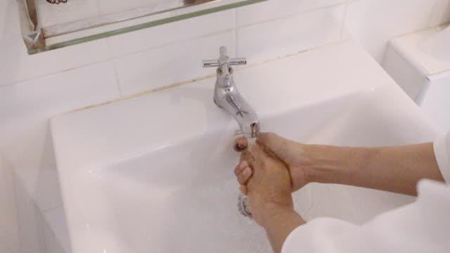 4K CU: vrouw handen wassen van de handen in de badkamer, close-up van handen