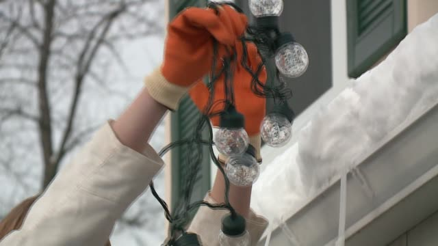 WGN Woman Hanging Christmas Lights Along House Gutter in Chicago on November 23 2015