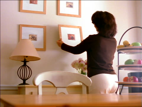 REAR VIEW woman hanging picture in frame on wall of house