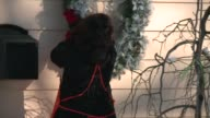 WGN Woman Hangs A Wreath On The Outside of a House in Chicago on November 23 2015