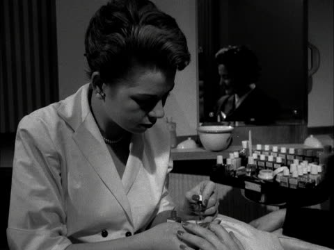 A woman has her nails painted by a manicurist 1955